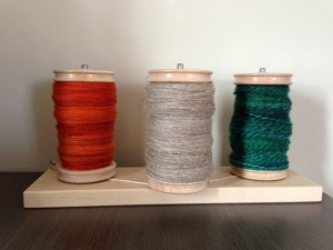 At left are some orange merino  singles, spun worsted, which  I need to do something with one of these days. Center are the silver Romney/Perendale singles spun long draw. At right is a three-ply I spun just yesterday out of some BFL singles I had spun on a drop spindle.