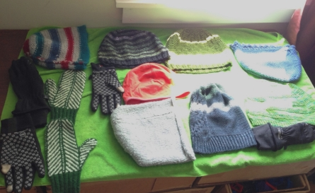 Knitted hats and mittens, plus a couple non-woolen gloves, drying in the sun.