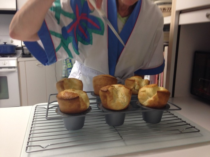 "And here's Mom ""stabbing"" the popovers to release the air."